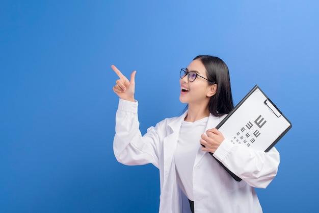 Una joven oftalmóloga con gafas sosteniendo un gráfico optométrico sobre azul, concepto de salud
