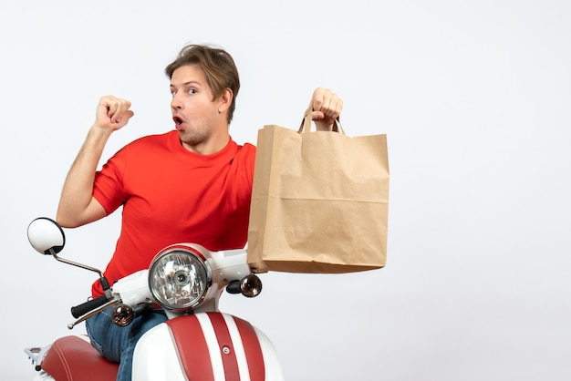 Joven orgulloso mensajero en uniforme rojo sentado en scooter sosteniendo una bolsa de papel en la pared amarilla