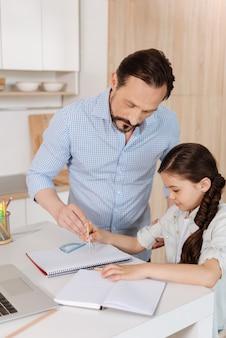 Joven padre barbudo ayudando a su encantadora hija pequeña a inscribir un círculo dirigiendo su mano con la de él.