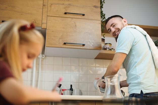 Joven padre barbudo lavando platos y sonriendo mientras mira a su padre que está dibujando en la cocina mientras la madre está trabajando.