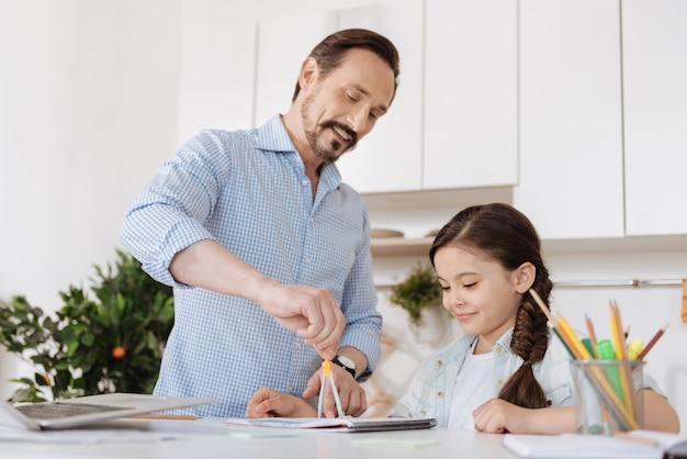 Joven padre barbudo sosteniendo un par de brújulas y mostrando a su bonita hija cómo usarlas mientras ella mira la herramienta con una linda sonrisa