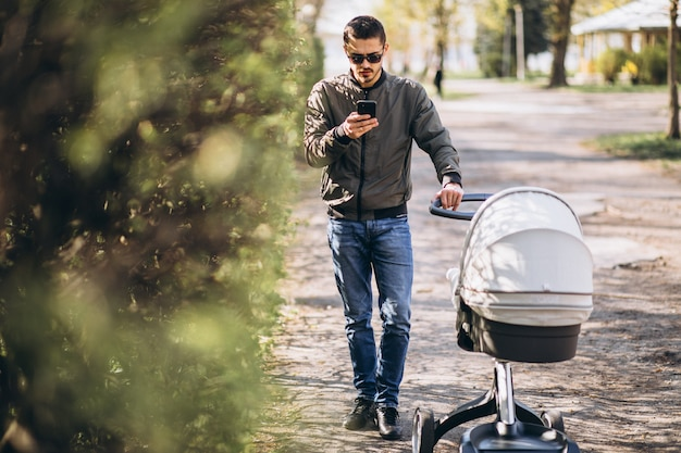 Joven padre caminando con carro de bebé en el parque