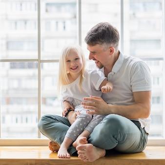 Joven padre divirtiéndose con su linda hija mientras está sentado frente a la ventana
