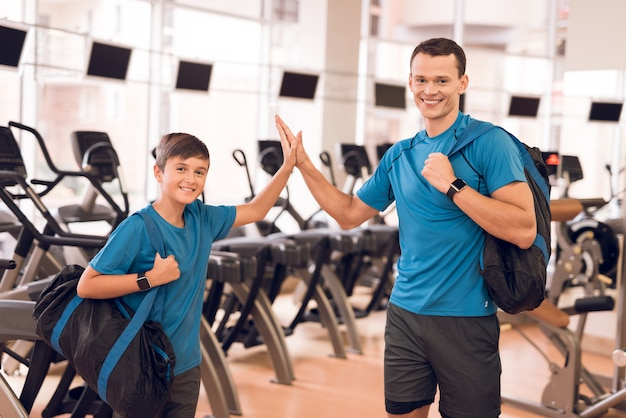 Joven padre e hijo cerca de cintas de correr en un moderno gimnasio