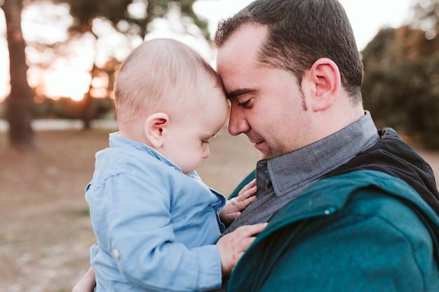 Joven padre e hijo jugando al aire libre al atardecer. concepto del día de la familia y el padre