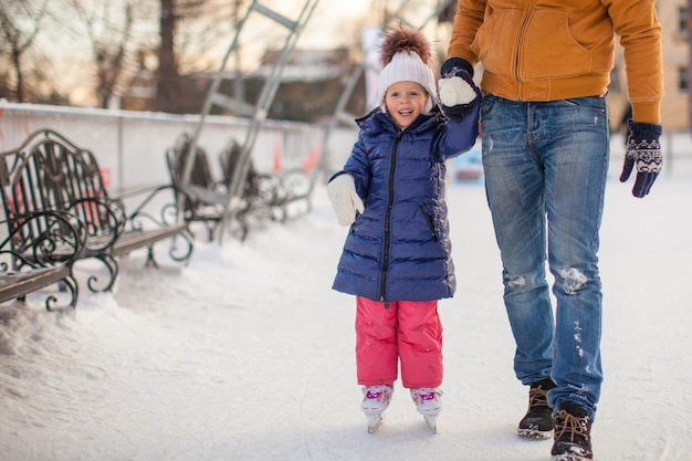 Joven padre enseñando a su pequeña hija a patinar en la pista