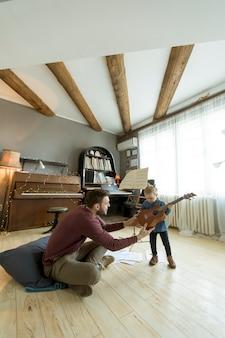 Joven padre enseñando a su pequeña hija a tocar la guitarra mientras está sentado en el piso de la habitación