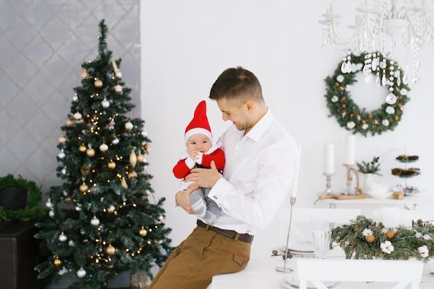 Joven padre feliz con su pequeño hijo en traje de santa cerca del árbol de navidad en la sala de estar
