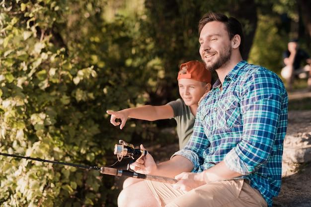 Joven padre con hijo en cap pesca en río.
