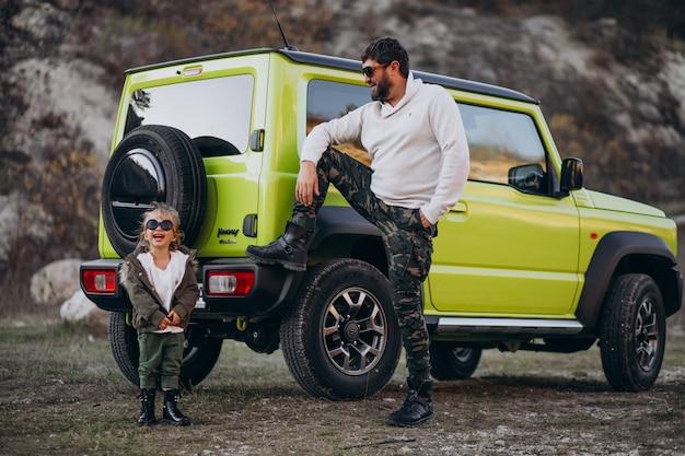 Joven padre de moda con su pequeña hija divirtiéndose en el coche
