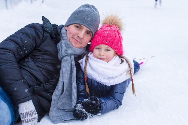 Joven padre y niña adorable en pista de patinaje al aire libre
