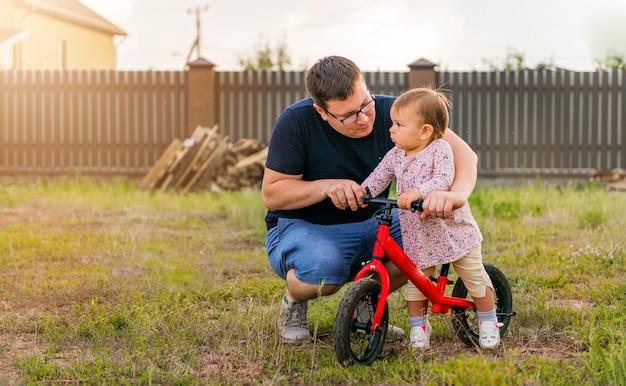 Joven padre pasa tiempo con una niña pequeña de un año de edad y una bicicleta de equilibrio.