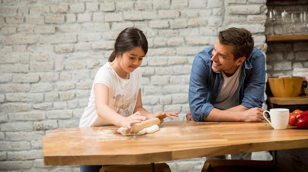 Joven padre y su linda hija haciendo masa en casa cocina