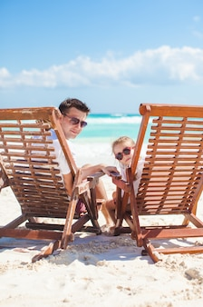 Joven padre y su maravillosa hija sentada en sillas de madera de playa mirando a la cámara