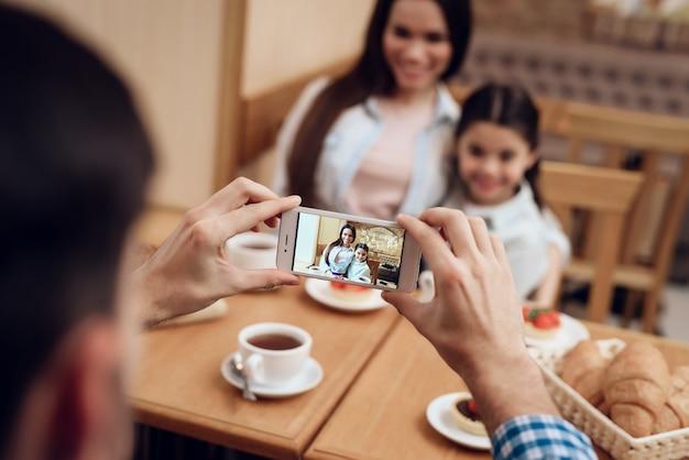 Joven padre tomando fotos de la familia en la cafetería.