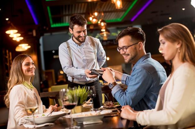 Joven pagando con tarjeta de crédito sin contacto en el restaurante después de la cena