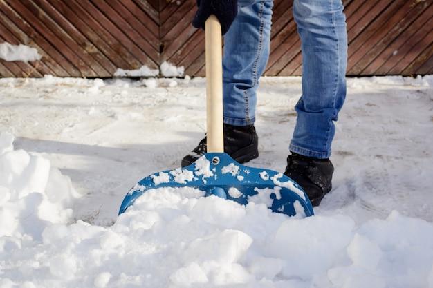 Joven palear la nieve en el camino de entrada cerca del garaje
