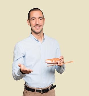 Joven con palillos para comer sushi
