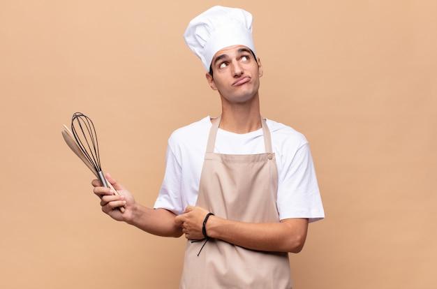 Joven panadero encogiéndose de hombros, sintiéndose confundido e inseguro, dudando con los brazos cruzados y la mirada perpleja