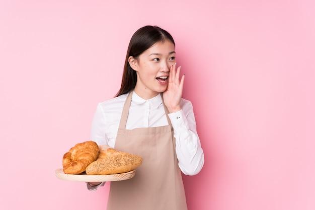 Joven panadero gritando y sosteniendo la palma cerca de la boca abierta