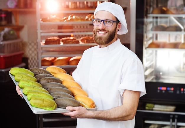 Joven panadero lindo en uniforme blanco sosteniendo una bandeja con rollos de colores para hot dog de panadería o fábrica de pan