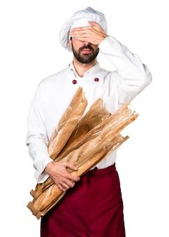 Joven panadero sosteniendo un poco de pan y cubriendo sus ojos