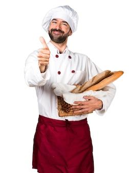 Joven panadero sosteniendo un poco de pan y con el pulgar hacia arriba