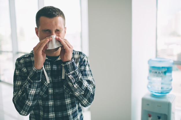 De un joven con pañuelo. el enfermo tiene goteo nasal. el hombre hace una cura para el resfriado común