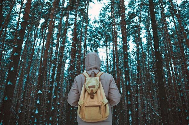 Joven parado en bosque nevado de invierno