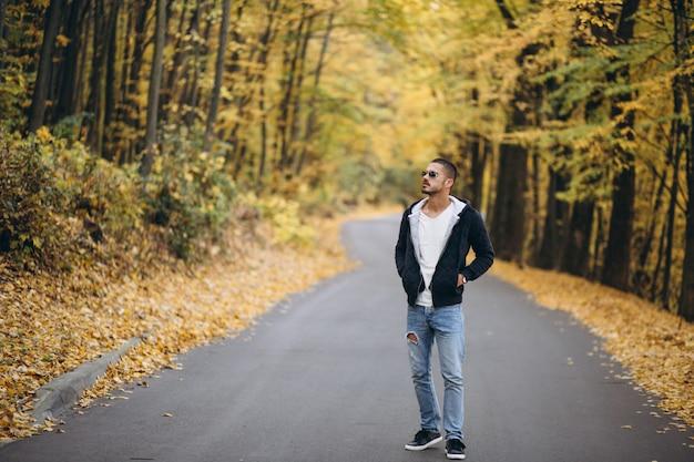 Joven parado en una carretera en un parque de otoño