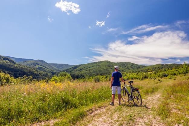 Joven parado cerca de la bicicleta en el amanecer de la mañana con maravillosos rayos y niebla de la mañana durante el día activo de verano tranquilo