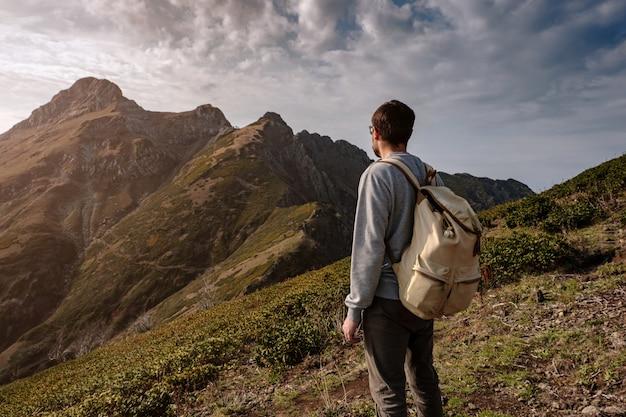 Joven parado en la cima de las montañas del acantilado
