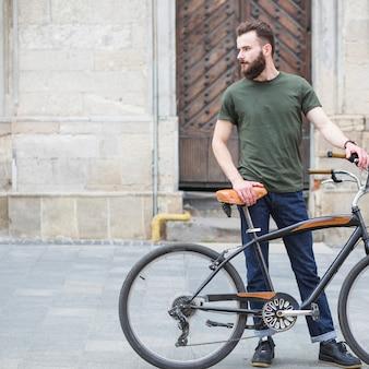 Joven parado con su bicicleta al aire libre