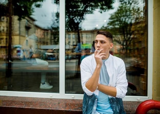 Joven parado fuera del restaurante fumando