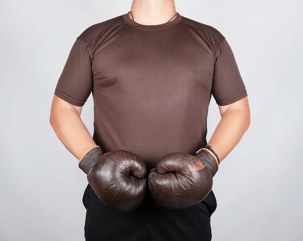 Joven está parado con guantes de boxeo marrón vintage muy viejos en sus manos