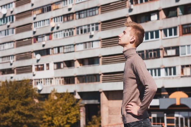 Un joven está parado con los ojos cerrados frente a un edificio de varios pisos.