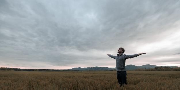 Joven parado en otoño pradera