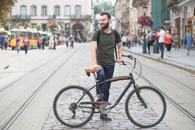 Joven parado con su bicicleta en la ciudad