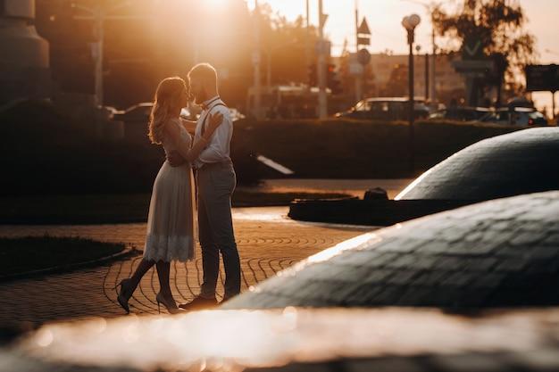Una joven pareja se abraza en la ciudad en una hermosa puesta de sol, estilo urbano.