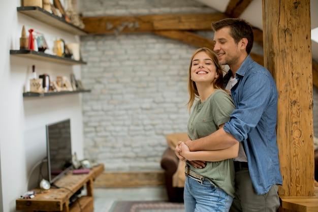 Joven pareja abrazándose en casa
