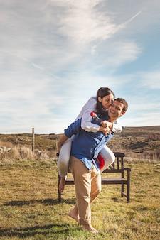 Joven pareja abrazándose y disfrutando de pasar tiempo juntos en el campo
