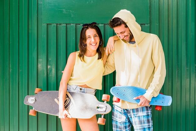 Joven pareja abrazándose de hipsters con patinetas