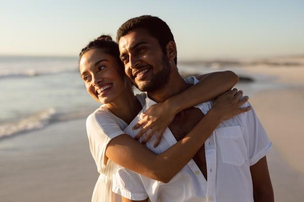 Joven pareja abrazándose en la playa