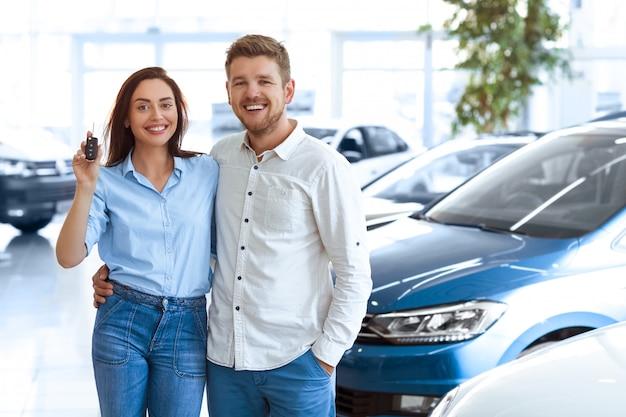 Joven pareja abrazándose en un salón del automóvil mostrando las llaves del auto a un vehículo recién comprado
