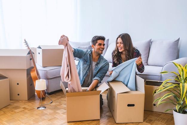 Joven pareja acaba de mudarse a un nuevo apartamento vacío desempaquetado y limpieza