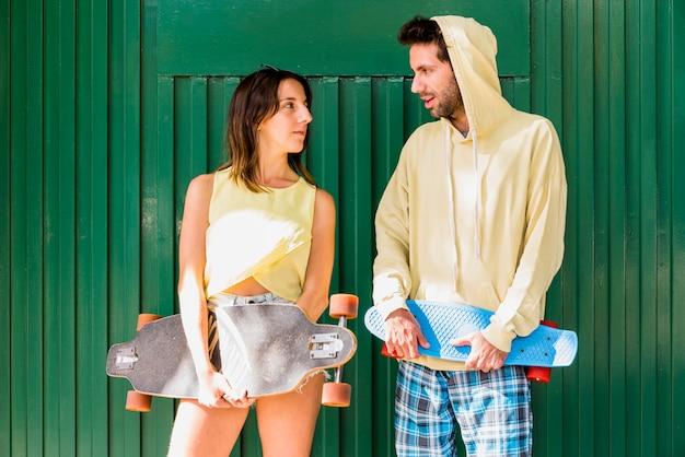 Joven pareja activa de amigos sosteniendo patinetas
