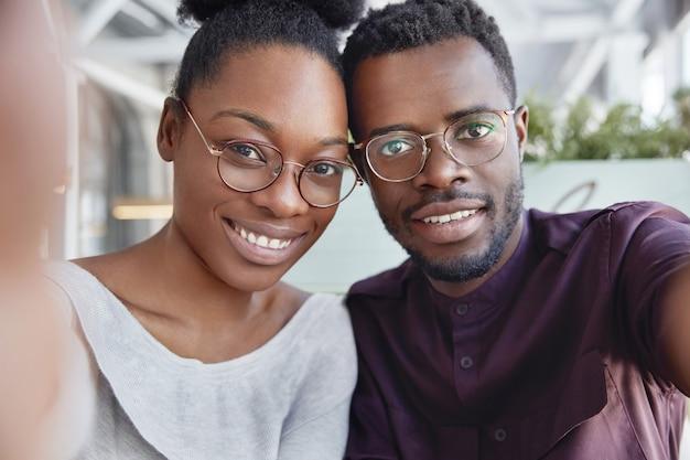 Joven pareja africana hace selfie, se para cerca el uno del otro, expresa emociones positivas, usa gafas.