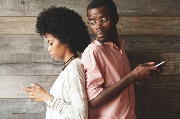 Joven pareja africana de pie espalda con espalda, sosteniendo teléfonos móviles