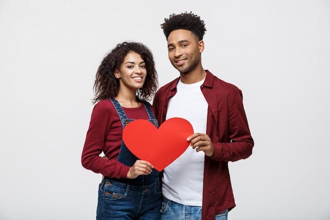 Joven pareja afroamericana feliz en el amor con corazón de papel rojo