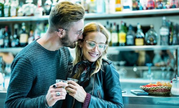 Joven pareja al comienzo de la historia de amor en el bar de cócteles - filtro verdoso